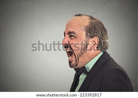 portrait of middle aged angry man screaming isolated on grey background  - stock photo