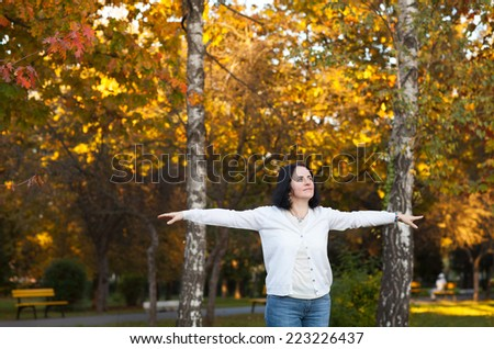 portrait of middle aged beautiful woman spreading her arms in park - stock photo