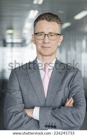 Portrait of middle-aged businessman standing with arms crossed in office - stock photo
