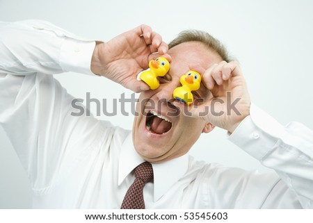 Portrait of middle aged  Caucasian businessman playing with rubber ducks making funny face. - stock photo