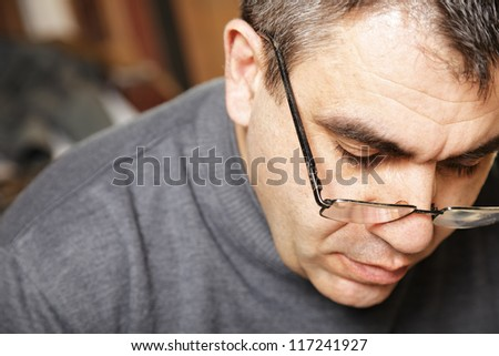 Portrait of middle-aged caucasian man in spectacles looking down front view - stock photo