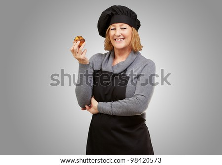 portrait of middle aged cook woman holding a delicious homemade muffin over a grey background - stock photo