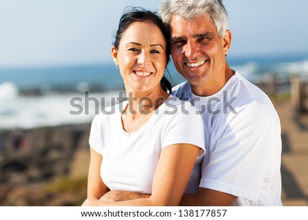 portrait of middle aged couple hugging at the beach - stock photo