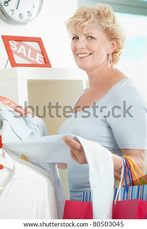 Portrait of middle aged customer looking at camera in clothing department - stock photo
