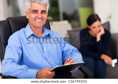 portrait of middle aged male psychologist in office with patient in background - stock photo