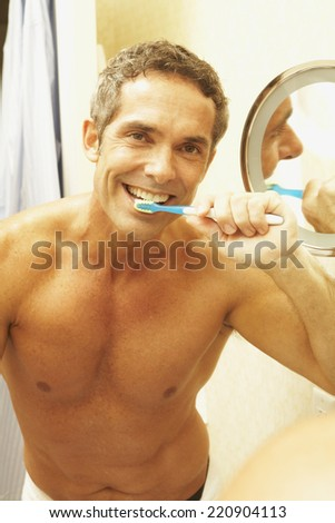 Portrait of middle-aged man brushing teeth - stock photo