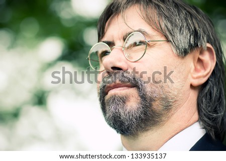 portrait of middle-aged man with glasses, looking  at copyspace - stock photo