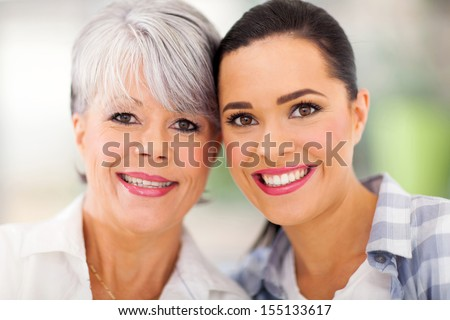 portrait of middle aged mother and young daughter at home - stock photo