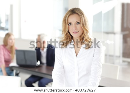 Portrait of middle aged professional businesswoman standing at office while her colleagues working at background. - stock photo
