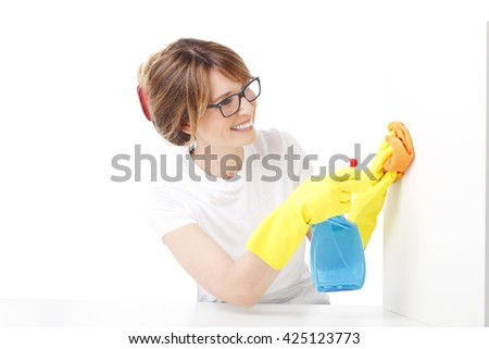 Portrait of middle aged woman holding a spray bottle and sponges in her hand while doing housekeeping. Isolated on white background.  - stock photo