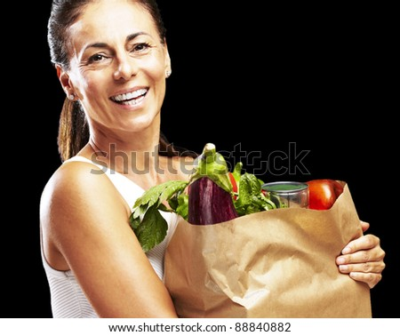 portrait of middle aged woman holding the purchase over black background - stock photo
