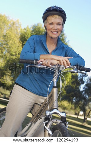 Portrait of middle aged woman standing with bicycle - stock photo