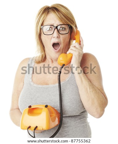 portrait of middle aged woman surprised talking on vintage telephone over white - stock photo