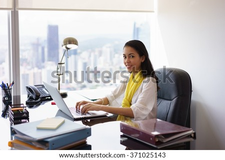 Portrait of mixed race business woman sitting in modern office in skyscraper. The secretary writes on laptop pc and smiles at camera. Medium shot