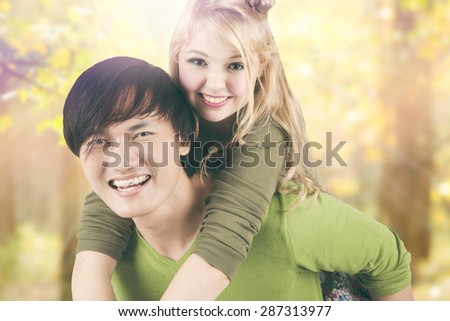 Portrait of mixed race couple enjoy summer holiday and having fun together in the park - stock photo