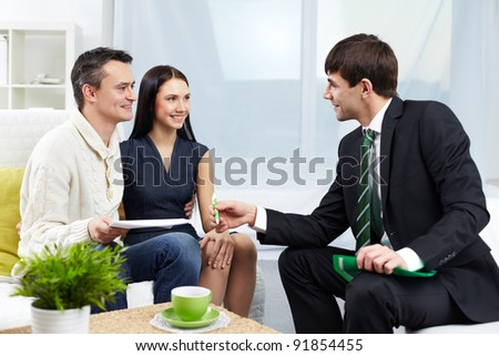 Portrait of modern couple looking at manager while discussing agreement - stock photo
