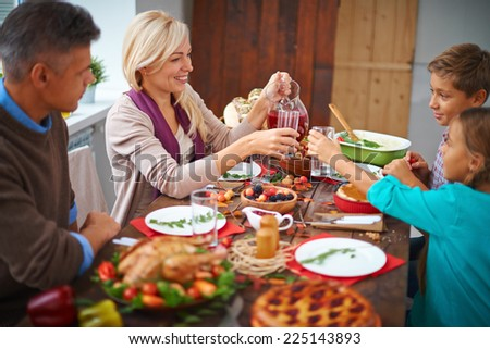 Portrait of modern family of four having festive dinner on Thanksgiving day - stock photo
