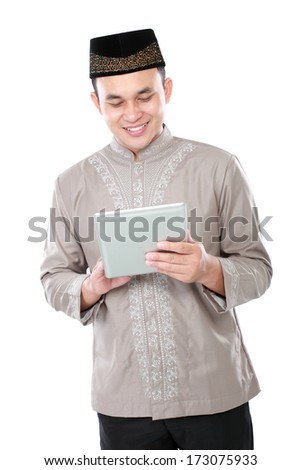 portrait of modern muslim man holding tablet pc isolated over white background - stock photo