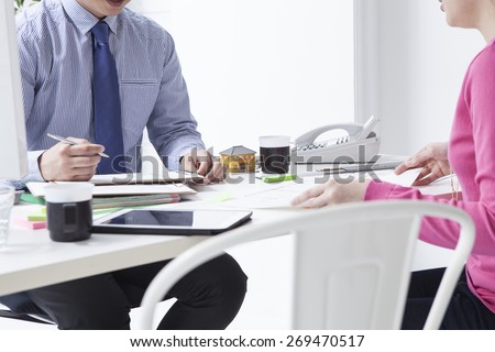 Portrait of modern woman and real estate manager discussing mortgage conditions - stock photo