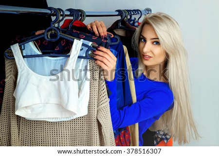 Portrait of modern young blonde girl with blue eyes and beautiful smile in clothing store. Beautiful young lady with a lot of clothes. Shopping concept. - stock photo