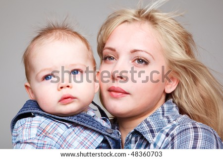 Portrait of mom and baby, on gray background - stock photo