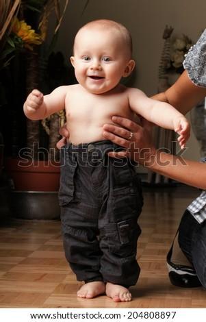 portrait of 6 months male child baby boy started beginning walking - stock photo