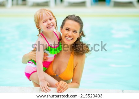 Portrait of mother and baby girl in swimming pool - stock photo