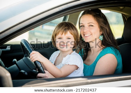 Portrait of mother and child pretend driving car sitting both on front driver seat - stock photo