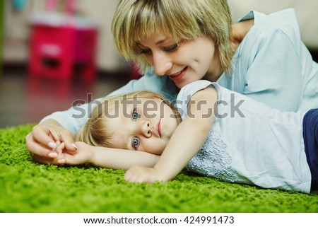 portrait of mother and daughter. child and mom playing at home. motherhood - stock photo