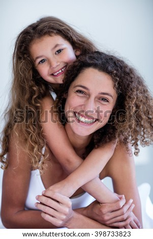 Portrait of mother and daughter embracing in bedroom - stock photo