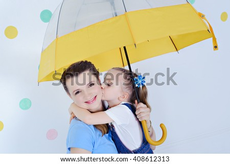 Portrait of mother and daughter, girl hugs mom and kisses her on the cheek, she's holding the umbrella, close-up, background in peas. - stock photo