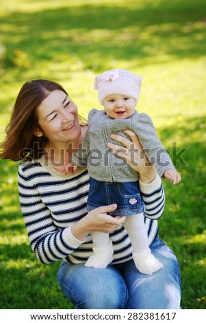 Portrait of mother and daughter, happy family of two, on the meadow in the park outside on a spring summer bright day, hugging, kissing and playing, mothers day concept holiday - stock photo