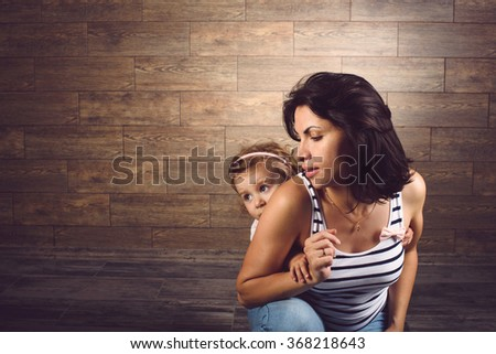 portrait of mother and daughter hiding behind her - stock photo