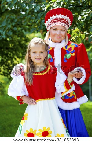 Portrait of mother and daughter in a national Russian costume on a background of green summer park - stock photo
