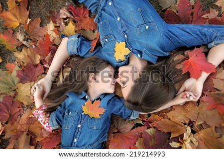 portrait of mother and daughter in the autumn - stock photo