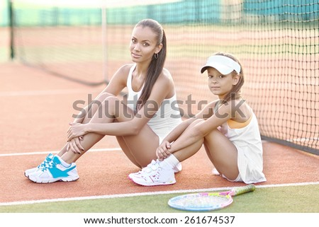 portrait of mother and daughter on the tennis court - stock photo