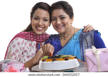Portrait of mother and daughter with birthday cake - stock photo