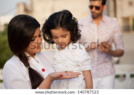 portrait of mother and daughter with father in the background, mother holding her daughter in the lap with father in the background - stock photo