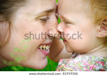Portrait of mother and her little baby playing - outdoors - stock photo