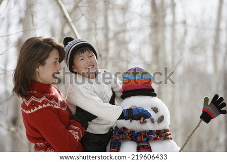 Portrait of mother and son building snowman - stock photo