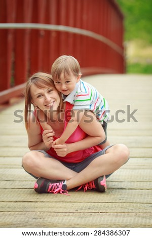 Portrait of mother and son together sitting on the wooden bridge and hugging  in forest countryside village smiling and laughing, happy family concept, summer fun activity - stock photo