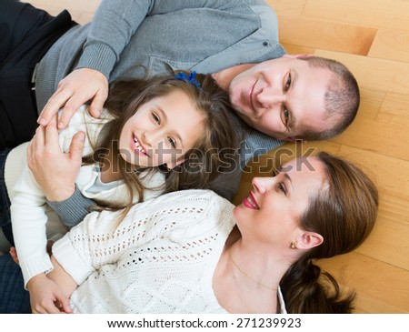 Portrait of mother, father and happy  girl together indoors - stock photo