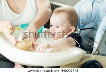 Portrait of mother feeding baby boy with fruit puree on kitchen - stock photo