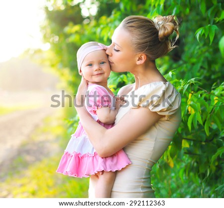 Portrait of mother hug and kissing baby daughter outdoors in sunny summer day - stock photo