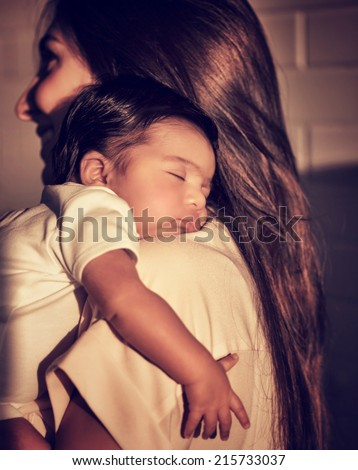 Portrait of mother standing back side and caring little sleeping baby on shoulders, enjoying mild sunset light, happy young family, peace concept - stock photo