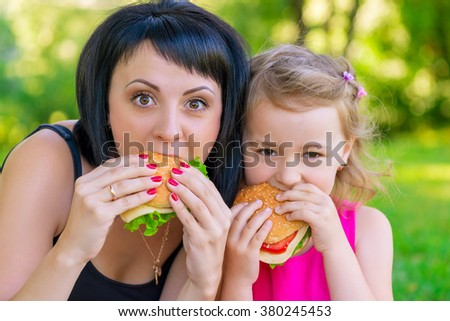 portrait of mother with her daughter in the park with burgers - stock photo