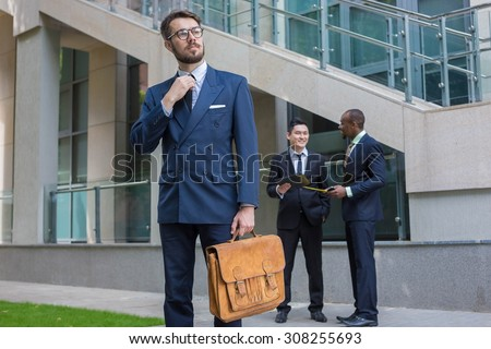 Portrait of multi ethnic business team.Three men standing against the background of city. The foreground of a European man. Other men is Chinese and African-American. The concept of success of the - stock photo