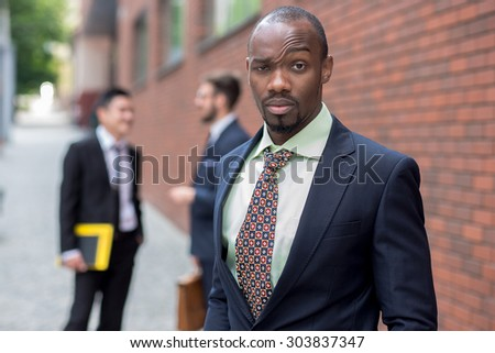 Portrait of multi ethnic business team.Three men standing against the background of red brick wall. The one doubtful man is  African-American. Other men is Chinese and European.  - stock photo