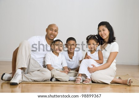 Portrait of multi-ethnic family on floor - stock photo