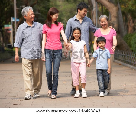 Portrait Of Multi-Generation Chinese Family Walking In Park Together - stock photo